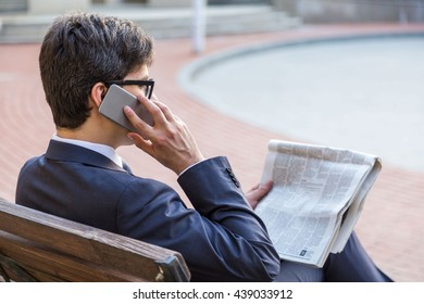 Young handsome businessman sitting on outdoor bench, holding newspaper and talking on phone