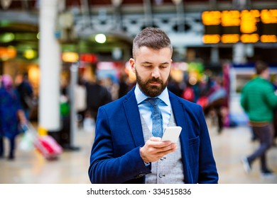 Young handsome businessman with smart phone standing at the crowded station