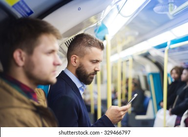 Young handsome businessman with smartphone in subway