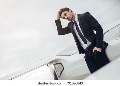 Young handsome businessman is standing near private plane. Confident and successful man in airport.