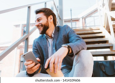 Young handsome businessman with stubble sitting on the stairs outside with his mobile phone