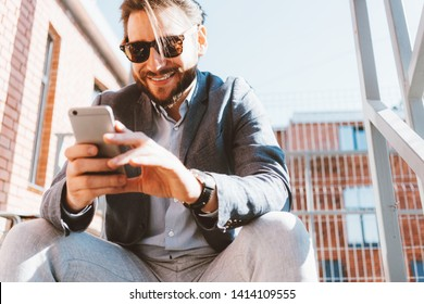 Young handsome businessman with stubble and sunglasses sitting on the stairs outside.  Smiling and looking at mobile phone