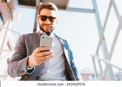 Young handsome businessman with stubble and sunglasses walking down the stairs outside. Smiling and looking at mobile phone