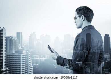 Young handsome businessman in suit and glasses using phone and thinking how to tackle the problem, new career opportunities, MBA. Bangkok on background. Double exposure.
