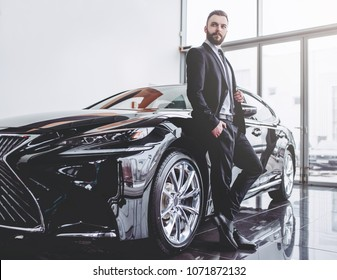 Young handsome businessman in suit is standing near car.