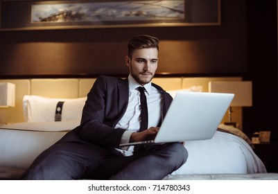 Young handsome businessman talks on-line with his business partners at the hotel room. Hotel service. Booking hotel. Freelancer sitting on his sofa in a hotel room and working with his computer.