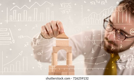 Young handsome businessman using wooden building blocks with white calculations scribbled around him