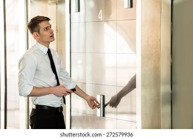 Young handsome businessman waiting on elevator of an business center.