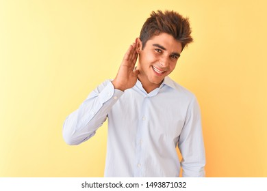 Young handsome businessman wearing elegant shirt over isolated yellow background smiling with hand over ear listening an hearing to rumor or gossip. Deafness concept.