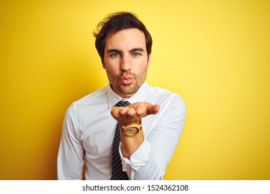 Young handsome businessman wearing elegant shirt and tie over isolated yellow background looking at the camera blowing a kiss with hand on air being lovely and sexy. Love expression.