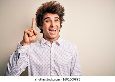 Young handsome businessman wearing elegant shirt standing over isolated white background pointing finger up with successful idea. Exited and happy. Number one.