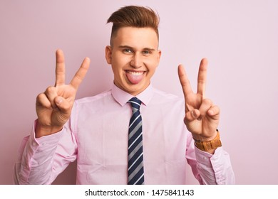 Young handsome businessman wearing shirt and tie standing over isolated pink background smiling with tongue out showing fingers of both hands doing victory sign. Number two.