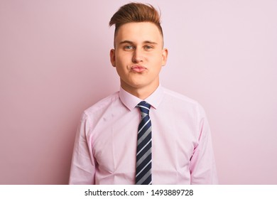 Young handsome businessman wearing shirt and tie standing over isolated pink background looking at the camera blowing a kiss on air being lovely and sexy. Love expression.
