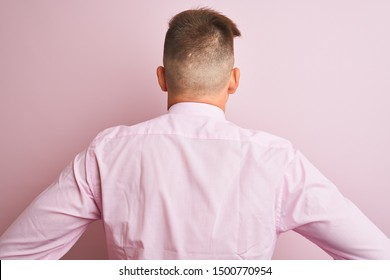Young handsome businessman wearing shirt and tie standing over isolated pink background standing backwards looking away with arms on body
