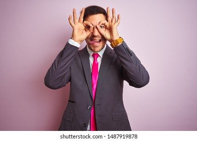 Young handsome businessman wearing suit and tie standing over isolated pink background doing ok gesture like binoculars sticking tongue out, eyes looking through fingers. Crazy expression.