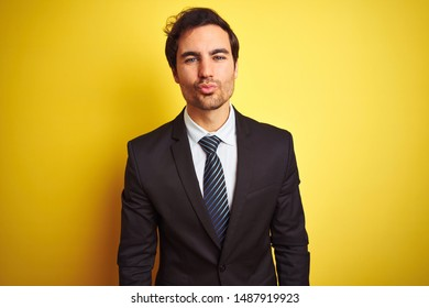 Young handsome businessman wearing suit and tie standing over isolated yellow background looking at the camera blowing a kiss on air being lovely and sexy. Love expression.