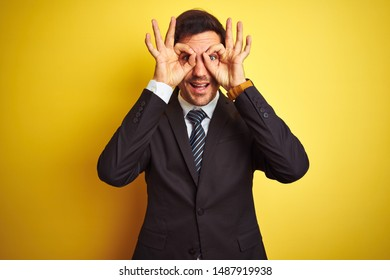 Young handsome businessman wearing suit and tie standing over isolated yellow background doing ok gesture like binoculars sticking tongue out, eyes looking through fingers. Crazy expression.