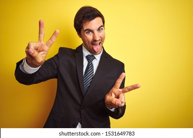 Young handsome businessman wearing suit and tie standing over isolated yellow background smiling with tongue out showing fingers of both hands doing victory sign. Number two.