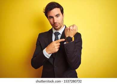 Young handsome businessman wearing suit and tie standing over isolated yellow background In hurry pointing to watch time, impatience, looking at the camera with relaxed expression
