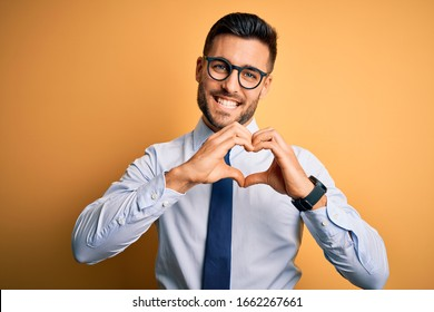 Young handsome businessman wearing tie and glasses standing over yellow background smiling in love doing heart symbol shape with hands. Romantic concept.