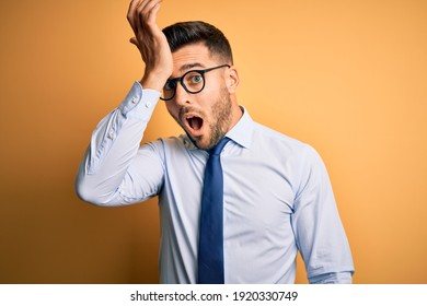 Young handsome businessman wearing tie and glasses standing over yellow background surprised with hand on head for mistake, remember error. Forgot, bad memory concept.