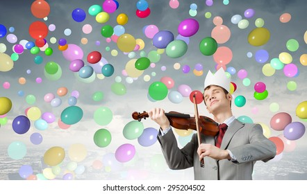 Young handsome businessman wearing white paper crown and playing violin