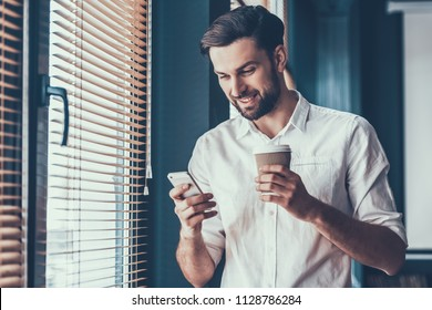 Young and Handsome Businessman in White Shirt with Cup of Coffe and Mobile Phone in Hands near Windows in Modern Office. Happy Office Worker at Work. Business Concept. Guy with Gadget.