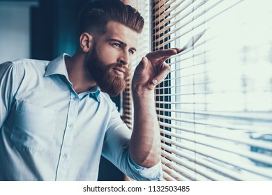 Young and Handsome Businessman in White Shirt near Windows in Modern Office. Bearded Young Man near Jalousie. Office Worker at Work. Business Concept. Work in Modern Office Concept.