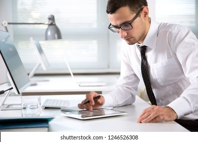 Young handsome businessman working with computer in an office
