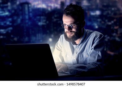 Young handsome businessman working late at night in the office with blue lights in the background