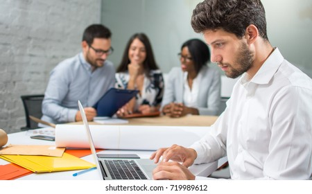 Young handsome businessman working on laptop with coworkers discussing a new project in the background.