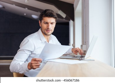 Young handsome businessman working and typing on laptop in the office
