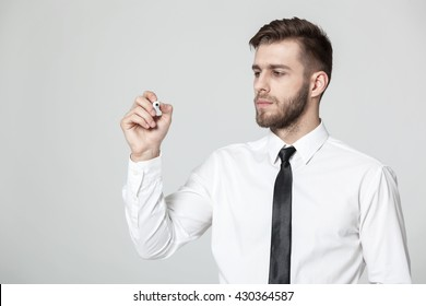 Young handsome businessman writing  on a transparent pane - copyspace.
