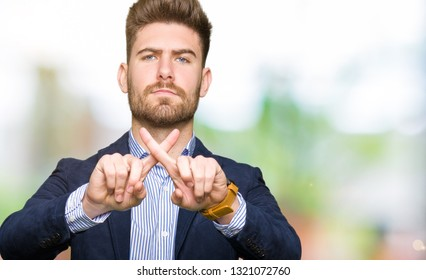 Young handsome bussines man Rejection expression crossing fingers doing negative sign