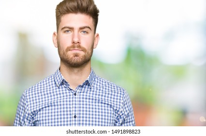 Young handsome bussines man with serious expression on face. Simple and natural looking at the camera.