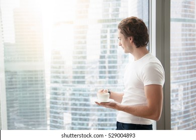 Young handsome carefree man near modern full length window enjoying a cup of coffee while looking outside, good morning, first day in a new office, free from work and duty, traveler. Copy space