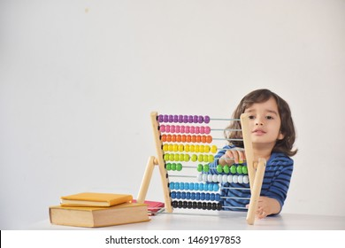 A young handsome Caucasian - Asian boy is love to using the abacus with coloured beads to learn how to count number in Kindergarten School - white background and copy space.