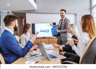 Young handsome caucasian bearded chief standing in boardroom, holding paperwork and having presentation. Other colleagues listening to him and and asking him questions.