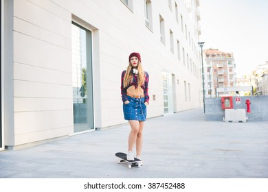 young handsome caucasian blonde straight hair woman model skater posing in the city backlight, headphones around her neck, looking in camera, serious - sportive, pensive concept