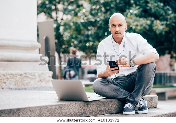 Young handsome caucasian businessman looking in camera with smart phone hand hold, listening music with earphones and computer leaning next to him - multitasking, business, technology concept