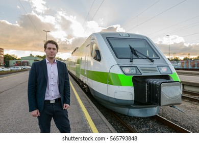 Young handsome Caucasian businessman standing in front of train at railway station