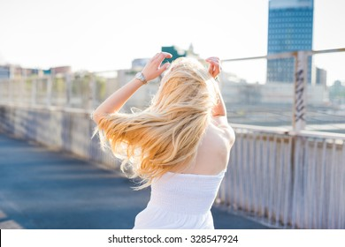 young handsome caucasian long blonde straight hair woman dancing in the city, view from back, feeling free in the city - dancing, freedom, youth concept
