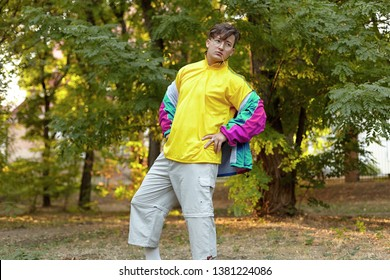 Young handsome caucasian man with bright freaky sportswear 70s style stands at a morning park. Stick in the mouth, golden glasses, earring and ring. Extravagance fashion. Outdoors, copy space.
