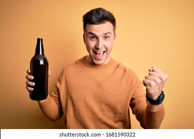 Young handsome caucasian man drinking a bottle of beer over yellow background screaming proud and celebrating victory and success very excited, cheering emotion