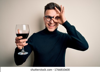 Young handsome caucasian man drinking an alcoholic glass of red wine over isolated background with happy face smiling doing ok sign with hand on eye looking through fingers