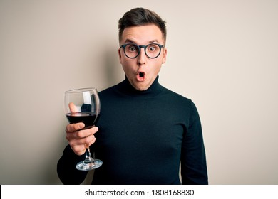 Young handsome caucasian man drinking an alcoholic glass of red wine over isolated background scared in shock with a surprise face, afraid and excited with fear expression