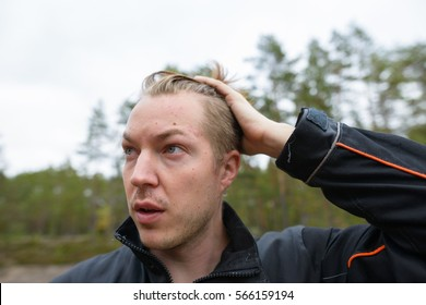 Young handsome Caucasian man fixing hair while thinking in the forest