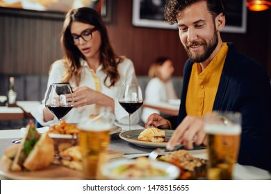 Young handsome Caucasian man having burgers for dinner while sitting in restaurant with his friends.