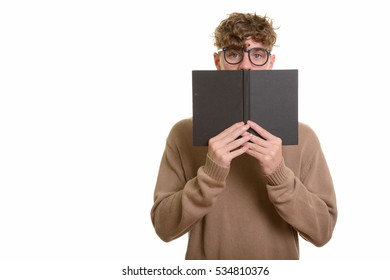 Young handsome Caucasian man hiding behind book