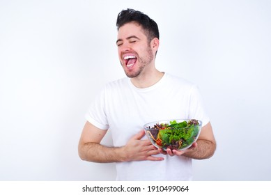 Young handsome Caucasian man holding a salad bowl against white background smiling and laughing hard out loud because funny crazy joke with hands on body.